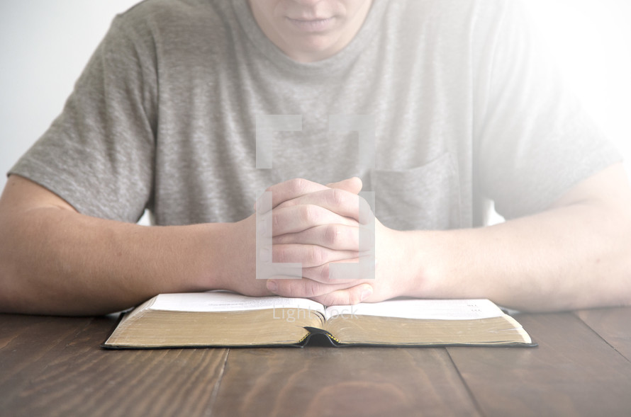 a man praying over an open Bible