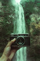 a camera in front of a waterfall