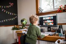 a child in front of a computer looking for Christmas music