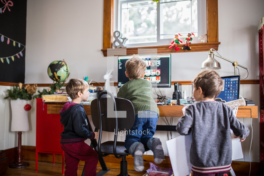 boys looking for Christmas music on a computer