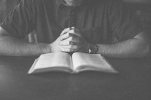 A man with hand folded in prayer in front of an open Bible