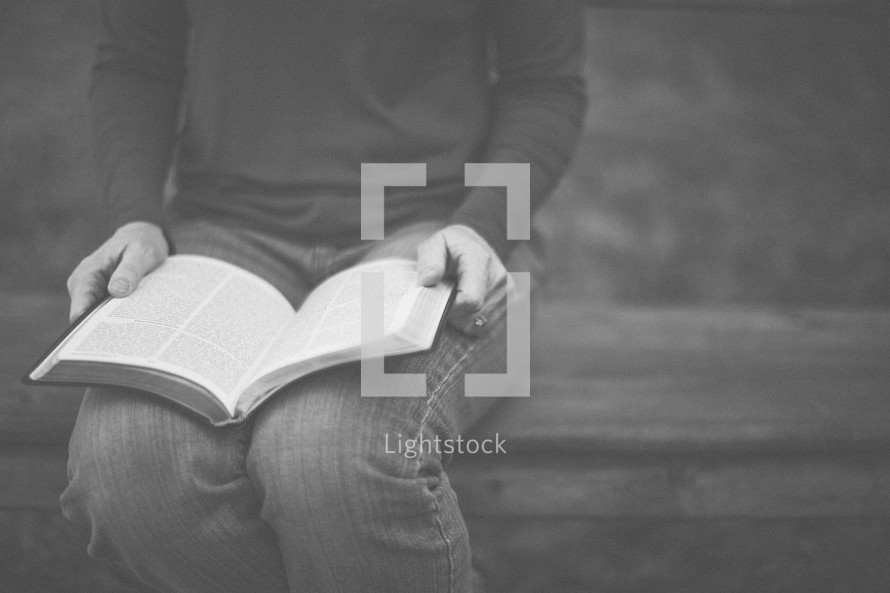 A woman sitting on a bench reading the Bible