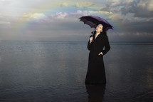 a woman holding an umbrella standing in water under a rainbow