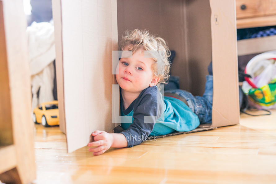 toddler boy playing with a cardboard box