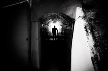 silhouette of a man in a dark tunnel
