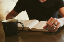 a man reading a Bible with a mug of coffee