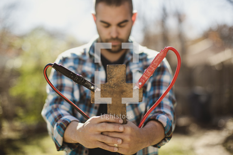 Man with eyes closed and head bowed holding cross with jumper cables attached.