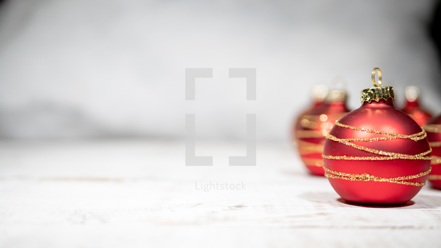 red ornaments on white wood boards