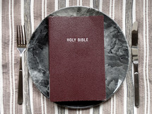 Holy Bible on a dinner plate.