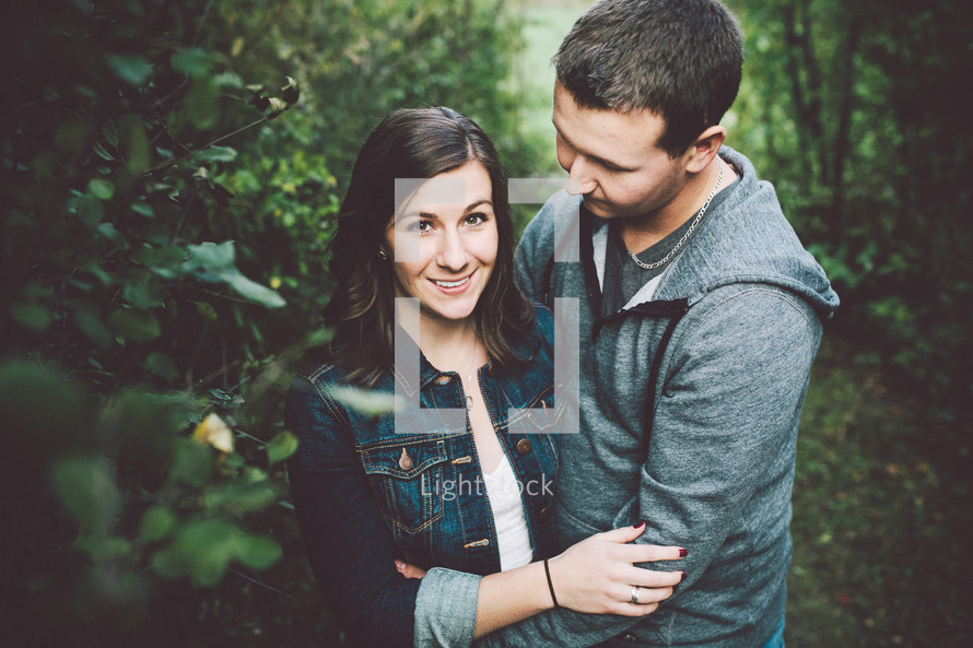 a young couple hugging outdoors