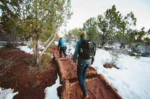 men backpacking on a path through snow