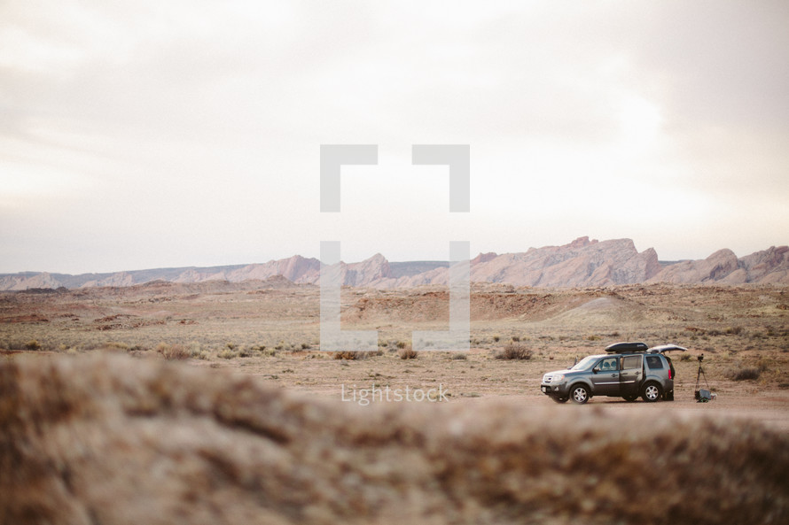an SUV and camera equipment in a mountainous desert