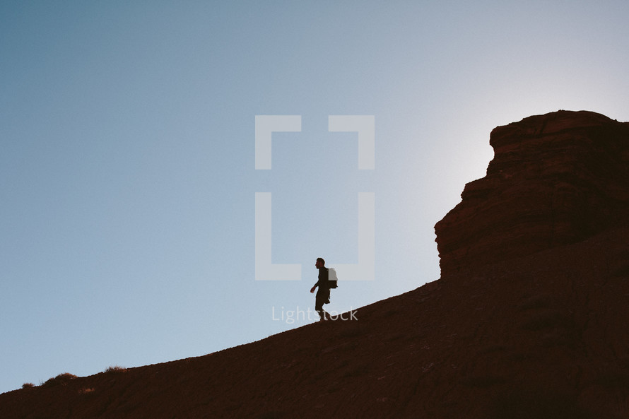 silhouette of a man hiking down a mountain