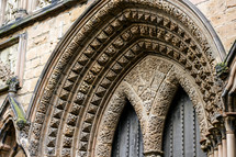 decorative stone archway over a cathedral door