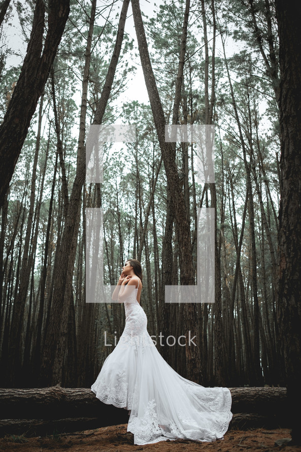 a bride standing in a forest