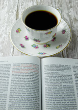 open Bible and floral print coffee cup
