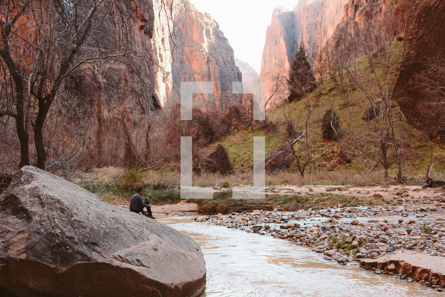 a man sitting in the bottom of a canyon