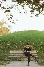 a man sitting on a park bench reading a Bible