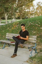 man sitting on a park bench reading a Bible