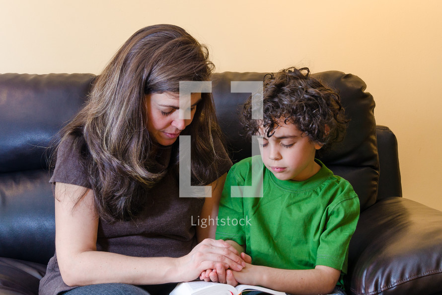 Mother and son praying together over the Bible.