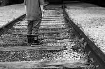 a boy in rain-boots standing on railroad tracks