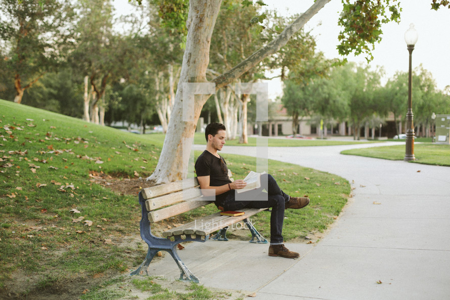 a man reading a Bible while sitting on a park bench
