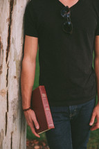 torso of a man leaning against a tree holding a Bible