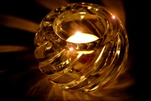 Burning candle in glass votive holder