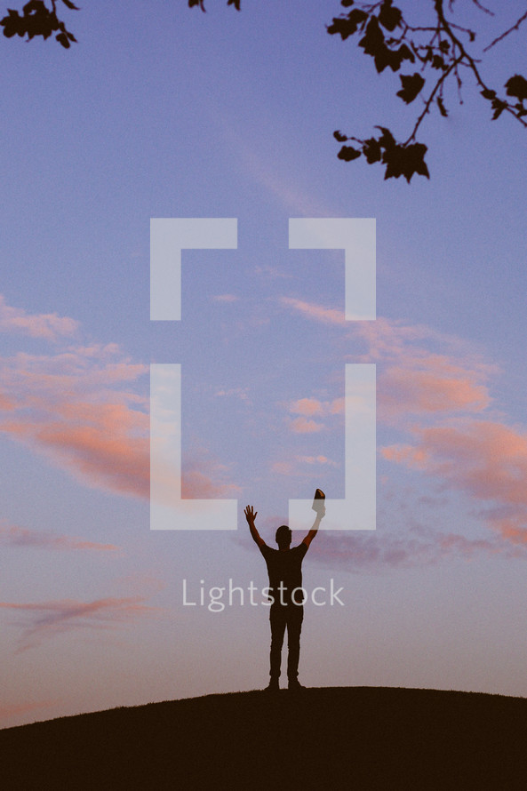silhouette of a man standing with raised hands holding a Bible