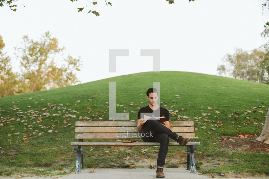 man reading a Bible while sitting on a park bench