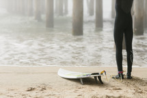 surfer standing next to a surfboard in the sand
