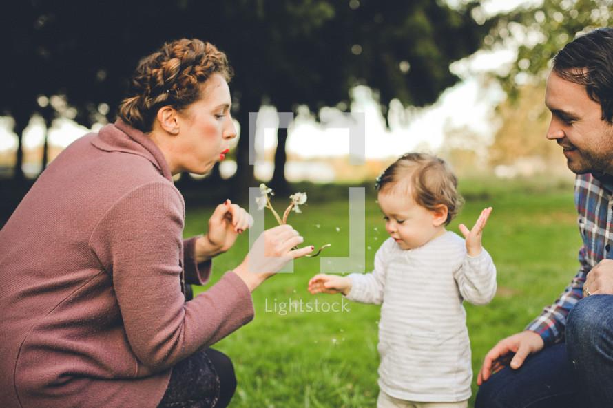 family blowing dandelions