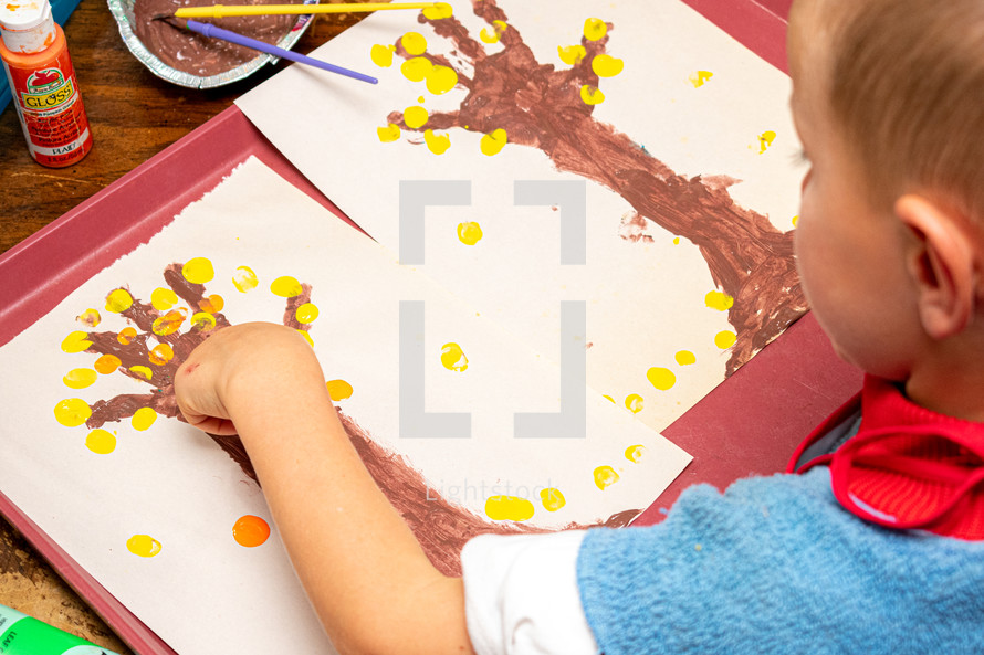 toddler finger-painting an autumn tree