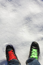 green and red shoe laces on a pair of black shoes standing in the snow