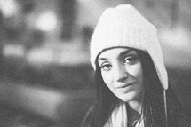 A young woman smiling in a white beanie