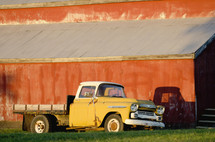 old flatbed truck parked in front of a red barn