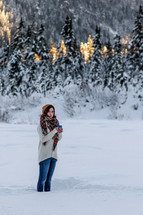 a woman standing in snow holding a warm mug