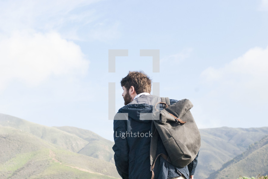 a man with a bag over his shoulders