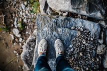 feet of a child standing on rocks