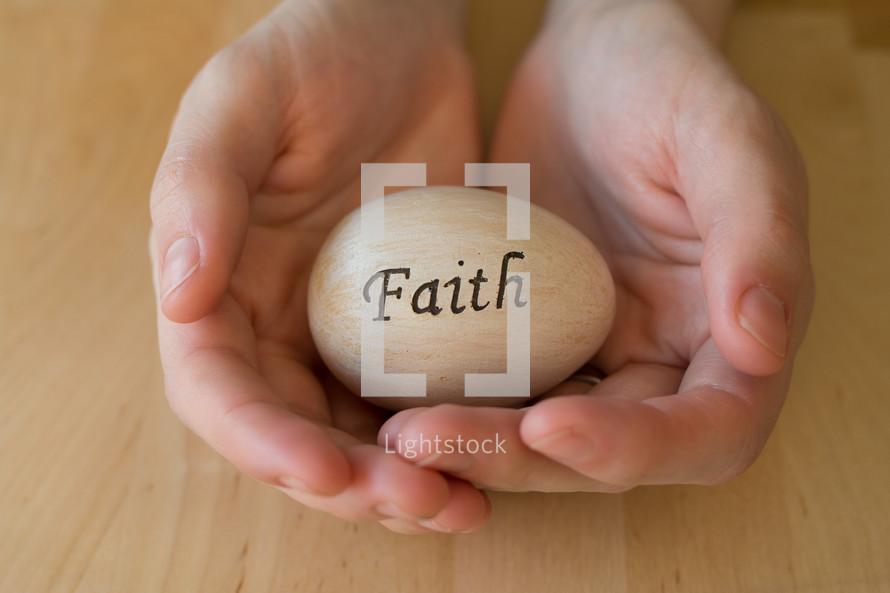 "Hands cradling an egg reading, ""faith."""