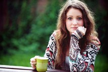 a young woman sitting drinking coffee