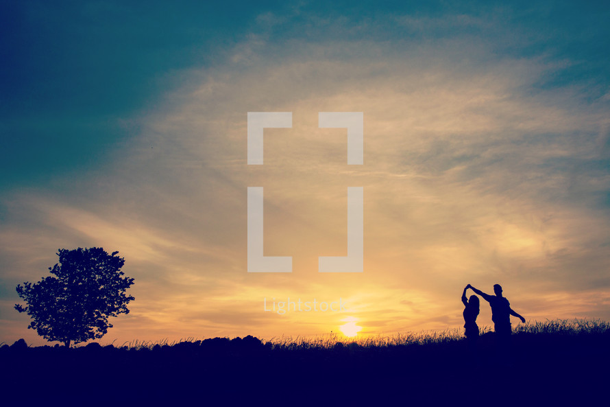 silhouette of a couple dancing at sunset