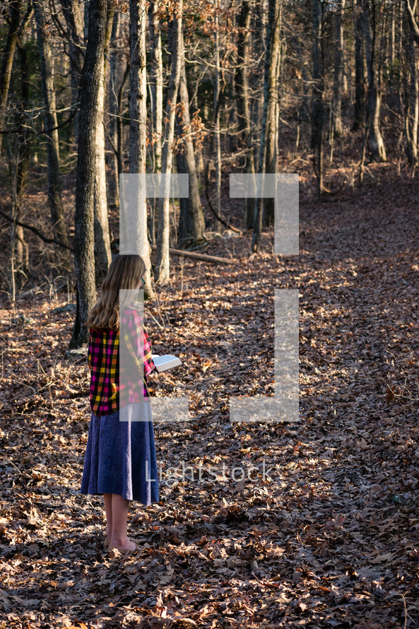 a girl standing outdoors reading a Bible