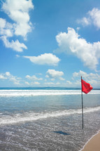 red flag warning on a beach