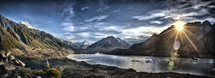 A sunburst over a mountain lake