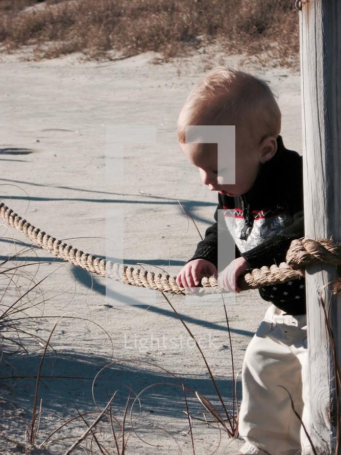 A curious toddler boy exploring a sand dune at the beach