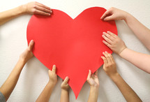 kids hands holding up a red heart