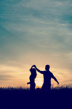 silhouettes of a couple dancing at sunset