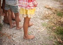 children's bare feet on gravel