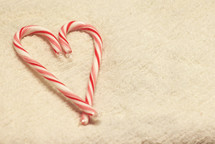 candy canes in snow in the shape of a heart